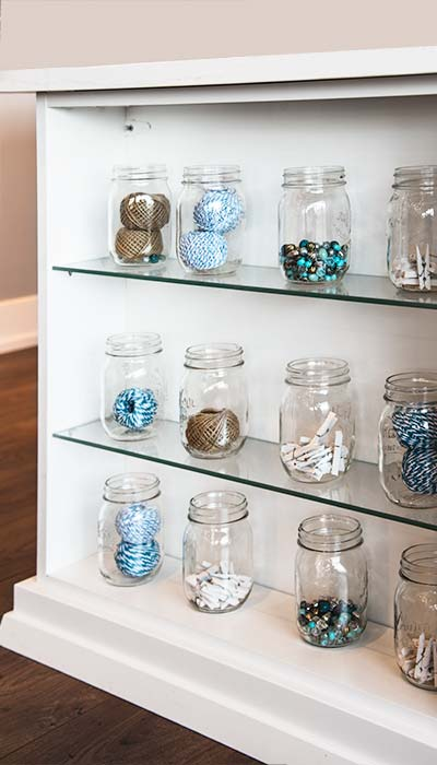 Glass shelves are both decorative and hold craft supplies