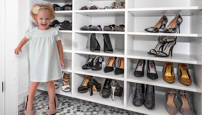 A child plays dress-up in her mothers shoe closet.