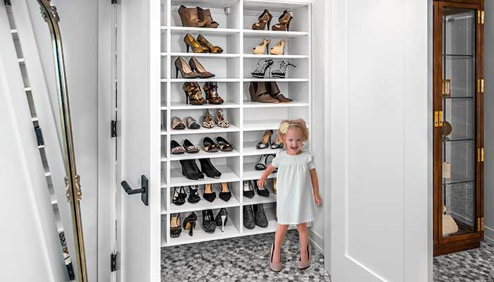 Little girl in front of closet wearing her mothers shoes