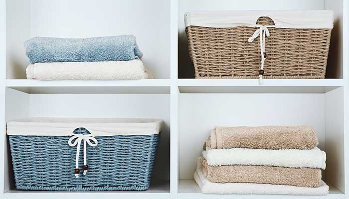 color coded linen closet with towels and baskets for toiletries