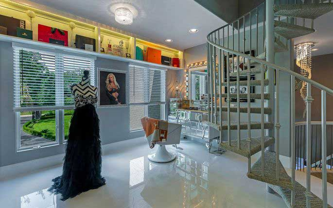 sculptural elements of this luxury closet include evening gowns and the staircase