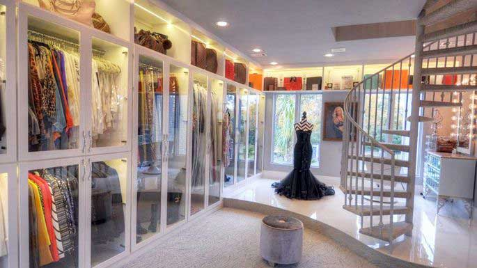 glass doors and a spiral staircase feature prominently in this luxury closet