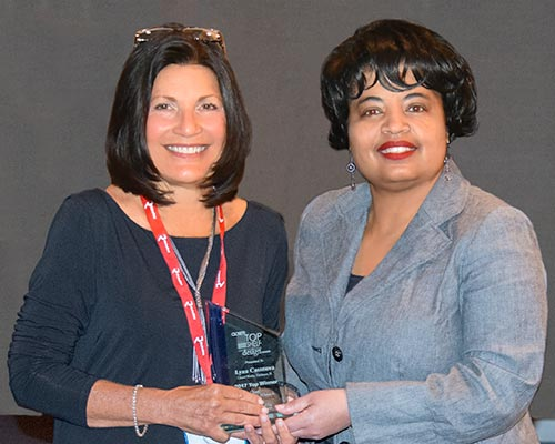 Lynn Casanova is presented with award by Michelle Bradford of Woodworking Network