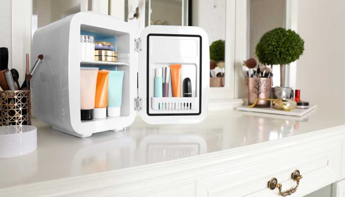 Mini refrigerator with makeup on top of vanity table