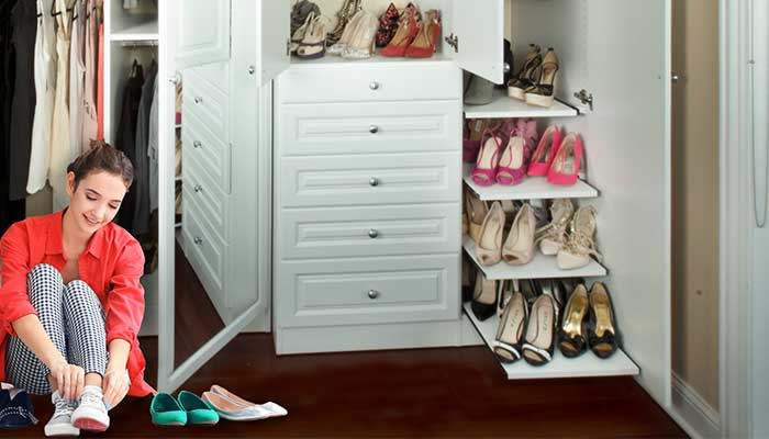 A woman puts on shoes in front of her shoe closet.