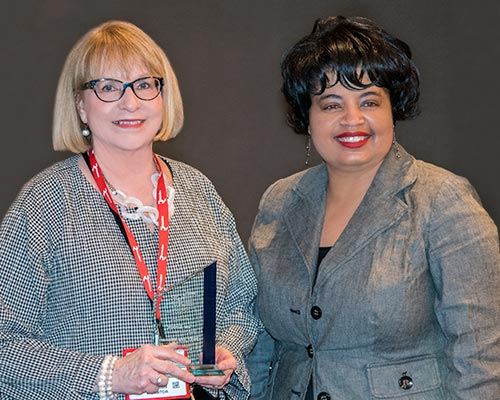 Sue Tinker is presented with award by Michelle Bradford of Woodworking Network