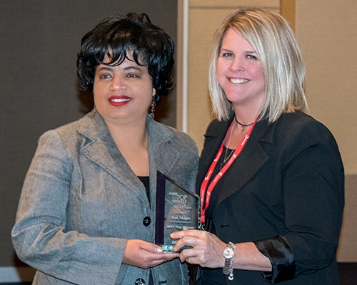 Teri Magee is presented with award by Michelle Bradford of Woodworking Network