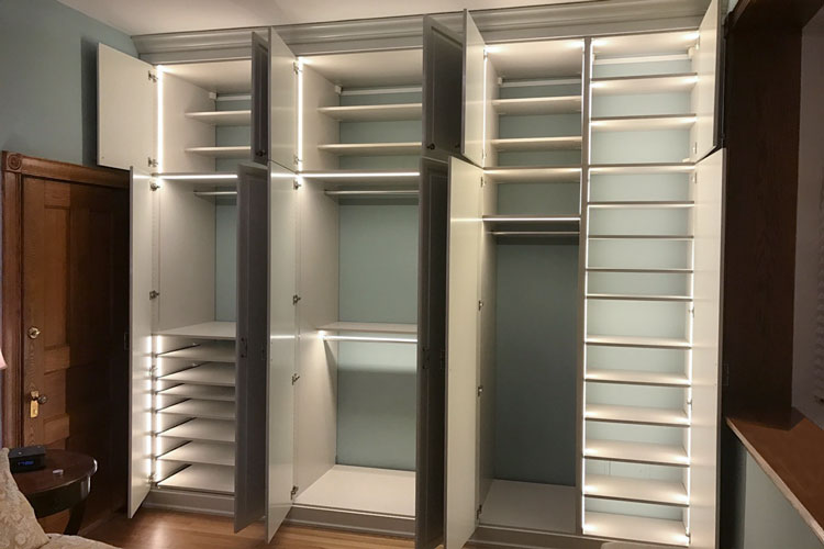 interior of bedroom closet storage systems with custom LED closet lights and pull out shelves