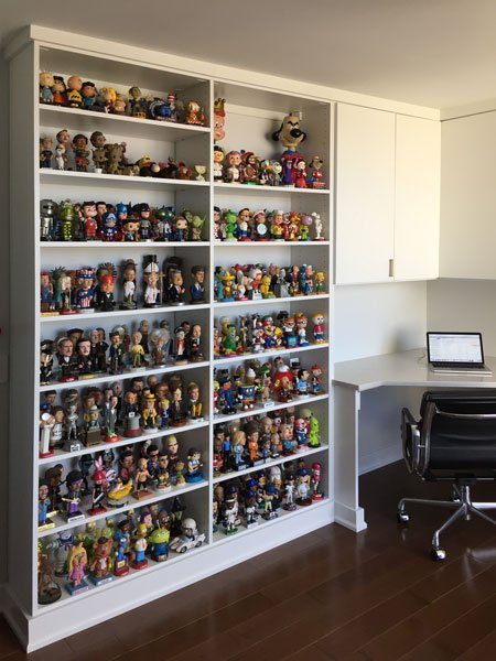 Home office with bookshelves full of bobbleheads