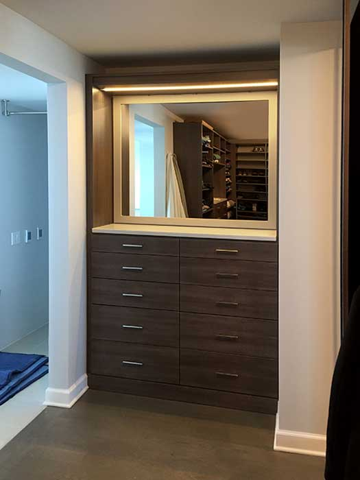 shared closet organization system with custom mirror and closet lighting