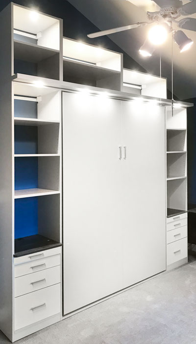 Closed Murphy bed and wall unit with storage for office supplies