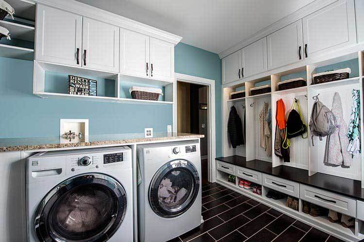 Custom laundry storage with cabinets and mud room organization system