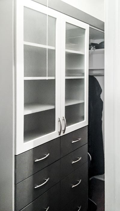 closet with reeded glass doors in Slate and white thermally fused laminate
