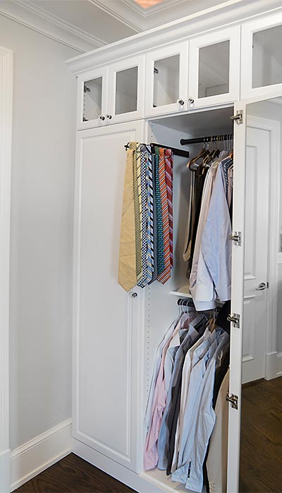 Detail built-in pull-out tie rack in custom bedroom wall unit