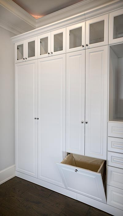 Detail of wall unit shows tilt hamper and laundry storage
