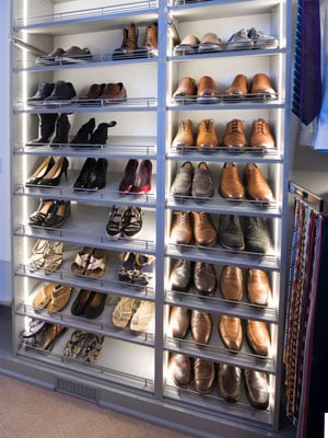Custom walk-in closet with LED slanted shelves with shoe fences