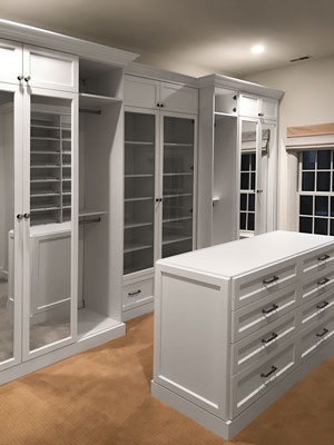 custom walk-in closet with white painted solid wood drawer faces