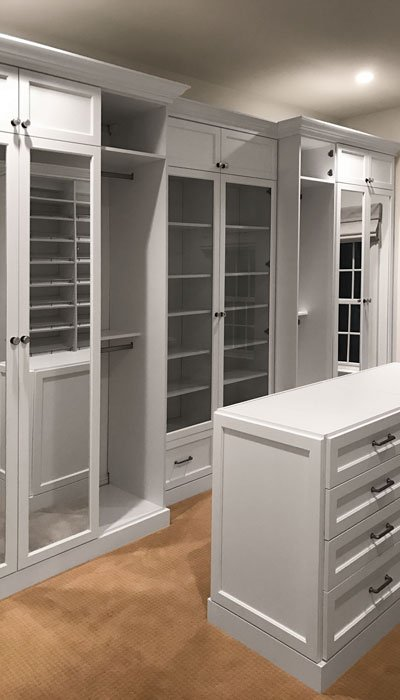 Large Walk In Closet With Custom Mirror Doors And Glass Cabinets