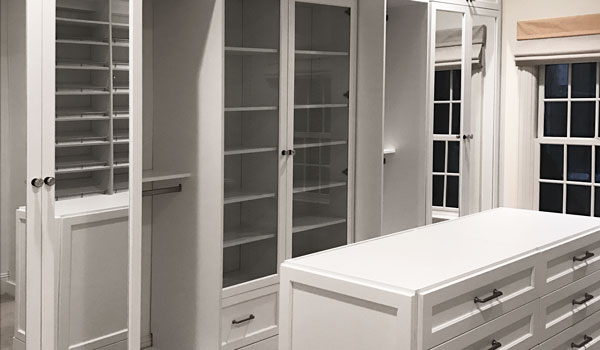 Custom walk-in closet designs with painted white drawer faces and molding