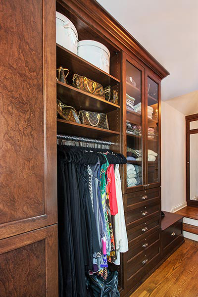 custom walkin closet organization system in natural wood with cocoa-cherry stain