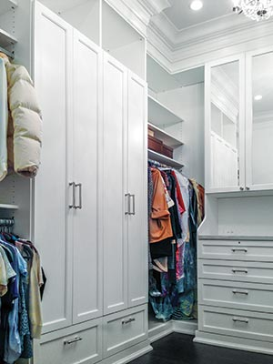 Master bedroom closet with hutch and wardrobe style armoirs inside the closet