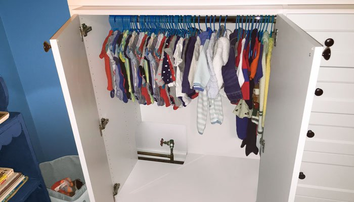 custom nursery closet with cabinets open show construction around gas pipe