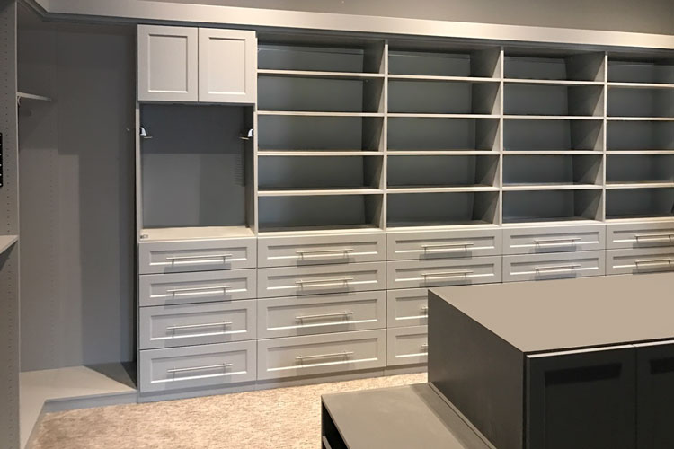 wall of shelves and closet with drawers for master walk in