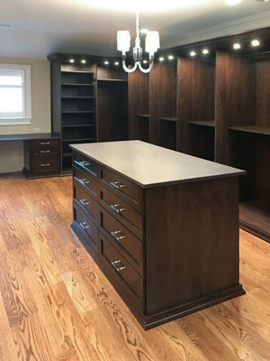 men's walk-in closet with custom lighting and island dresser