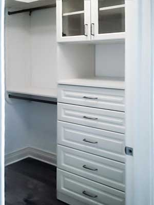 custom walk-in closet design shows closet hutch with glass doors
