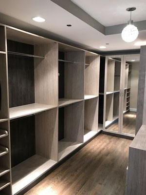 walk-in closet with different wood textures and crystal handles