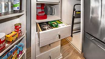 View of pantry drawer, step stool and shelf storage