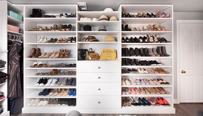A wall of shoes inside a large walk-in closet.