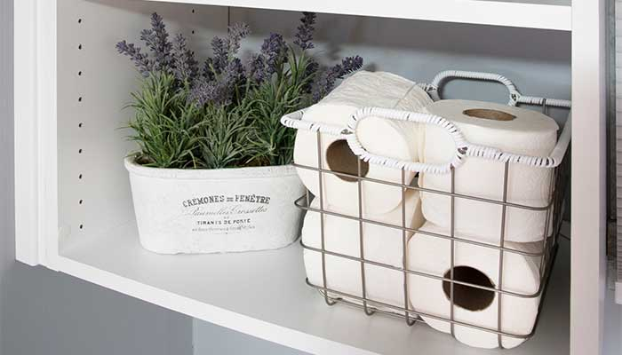 Toilet paper stored in decorative baskets.
