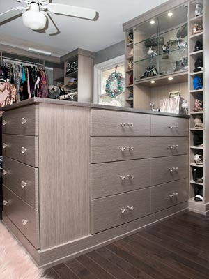 open closet with closet island with glass cabinets and glass shelving