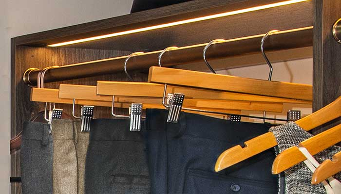 Under shelf strip lighting above clothes rod in closet illuminates clothes