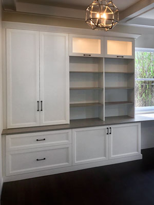 white wall unit with glass panel flip up doors and lights