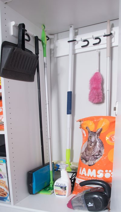 Utility closet offers storage for mops and brooms with 4-stick organizers