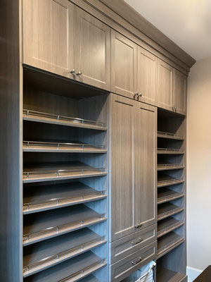 master walk in closet with slanted shelves and shoe fences