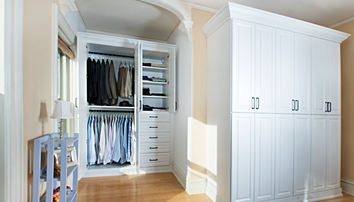 organized built in closet with additional armoire style wardrobe closet