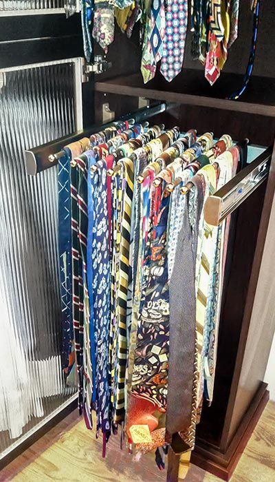 Small apartment ideas include glass closet cabinet for storage of neckties