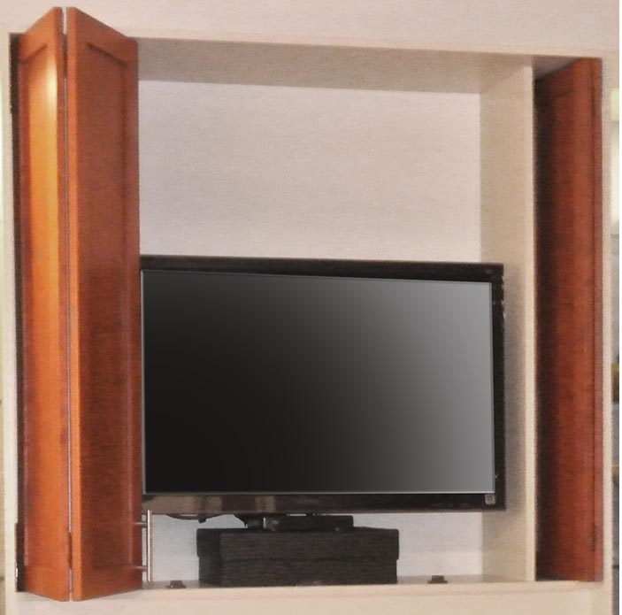 Detail of custom cabinetry in fireplace wall unit to hide television and media center components