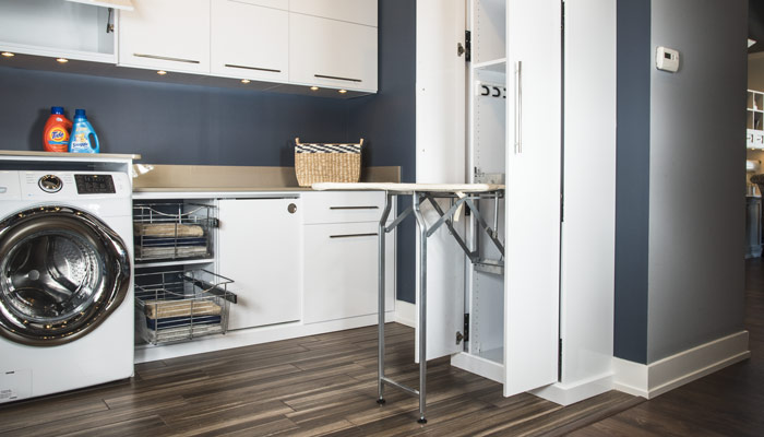 modern laundry room design with custom storage cabinets and pull-out accessories