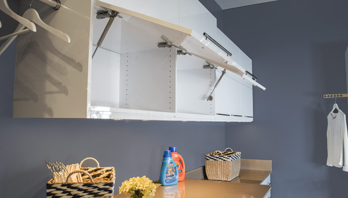 Awning style overhead doors flip up for easy access on custom laundry cabinets