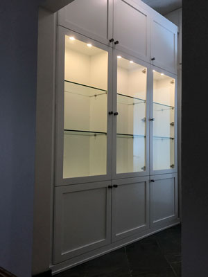 white bookcase with unity wood fronts with solid wood molding with glass shelves and laminate panels
