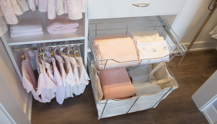 closet organizer system includes pull-out hamper and drawer for baby clothing