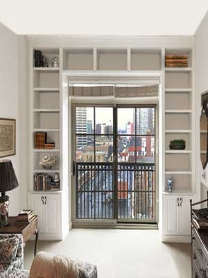 Wall of bookshelves surround patio door and create focal point