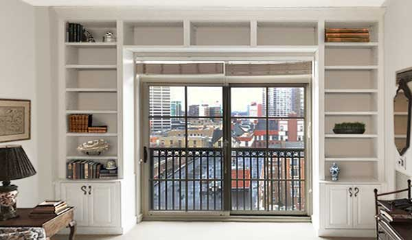 custom wall of bookshelves surrounds patio door and frames view