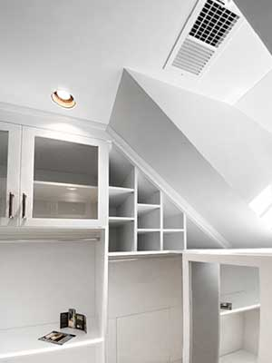 Walk-in closet with dormered ceiling.