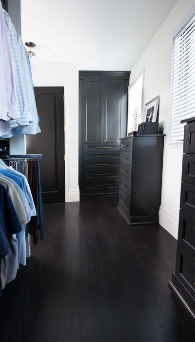 custom walk in closet with built-in armoire and dressers