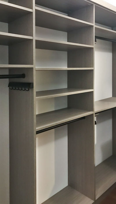 custom master walk in closet with shelves for folded sweaters and belt rack